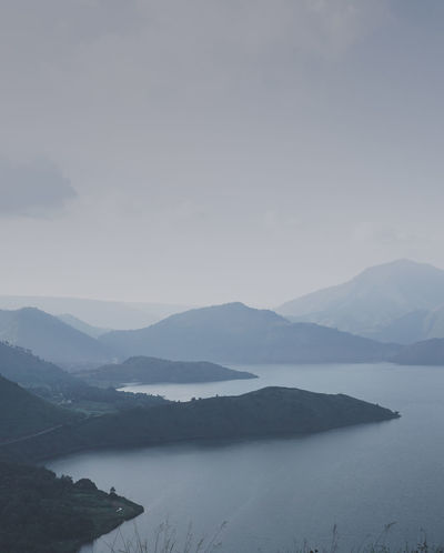 hills behind lake toba Mountain Scenics - Nature Beauty In Nature Tranquil Scene Tranquility Water Mountain Range Fog Non-urban Scene Idyllic No People Lake Nature Environment Landscape Remote Day Outdoors Hazy  Sky Blue Sky