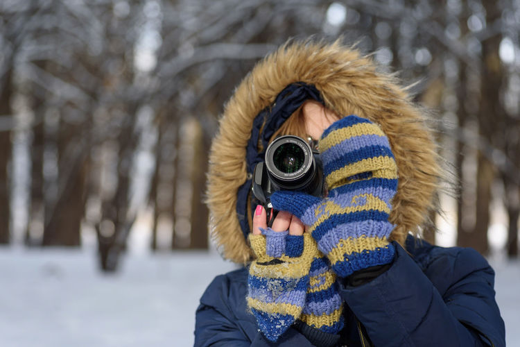 Midsection of woman photographing with snow
