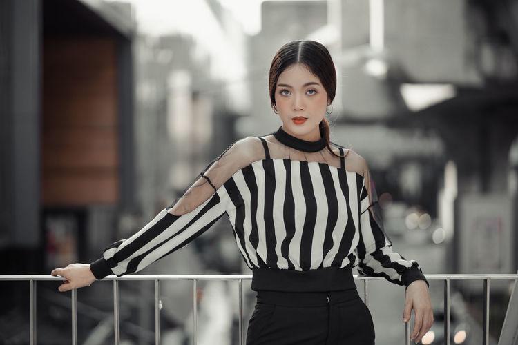 Portrait of beautiful woman standing against railing