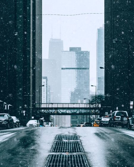 Road by buildings in city during winter