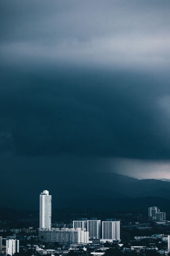 Buildings in city against storm clouds