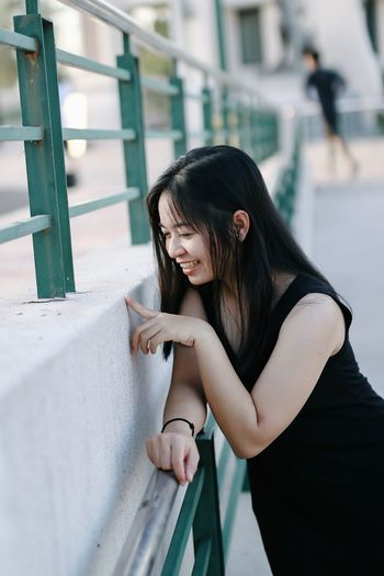 Smiling young woman standing by railing outdoors
