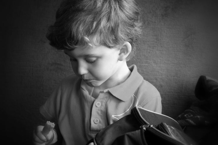 Close-up of boy holding felt tip pen while sitting against wall