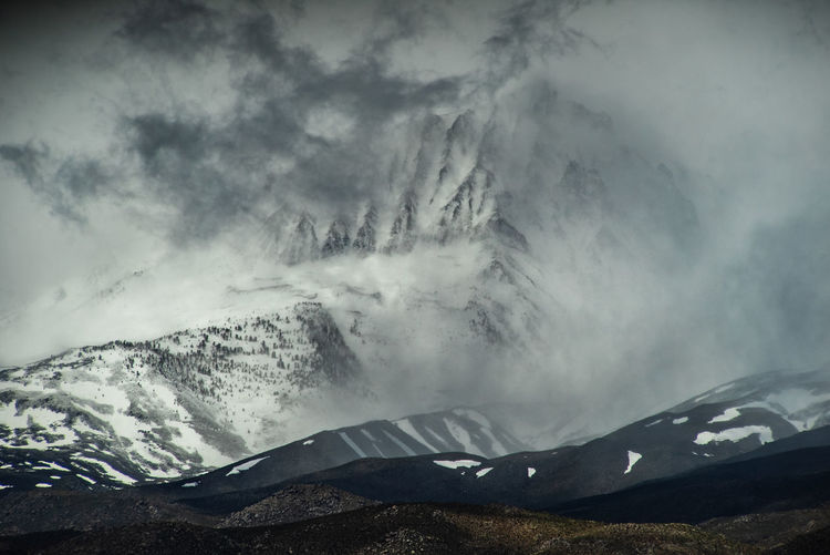 Snowcapped mountains against sky during foggy weather