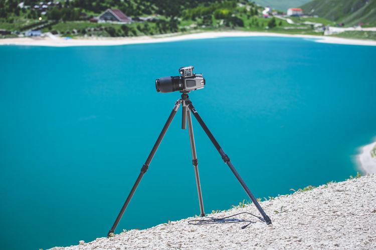Crane photographing sea against blue sky