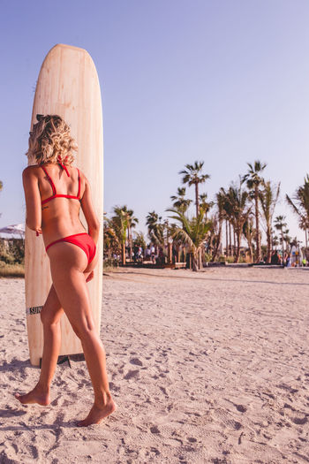 Rear view of woman in bikini on beach against sky