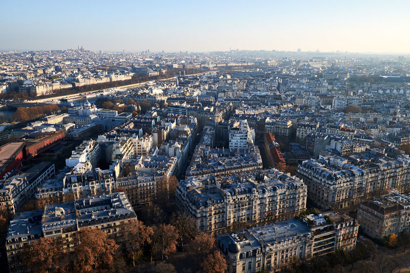 Aerial view of cityscape on sunny day against sky