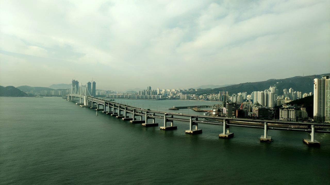 architecture, built structure, building exterior, sky, waterfront, connection, water, bridge - man made structure, river, city, transportation, cloud - sky, travel destinations, outdoors, day, no people, cityscape, skyscraper, mountain, nautical vessel, nature