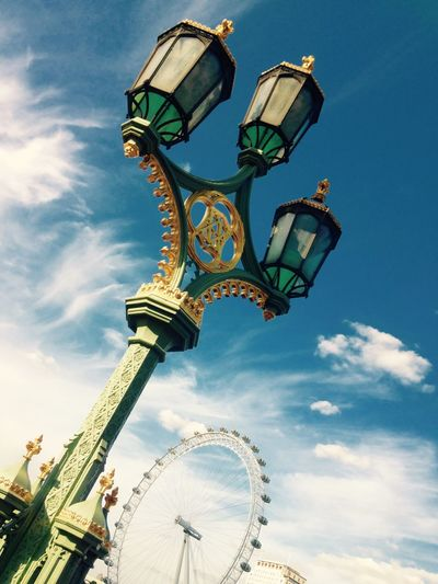 Low Angle View Of Street Light And London Eye Against Sky