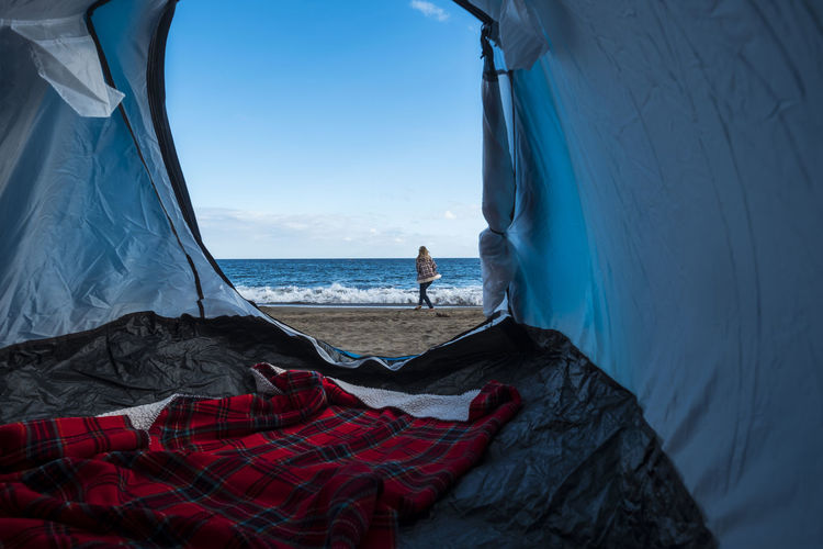 Woman walking on shore at beach seen through tent