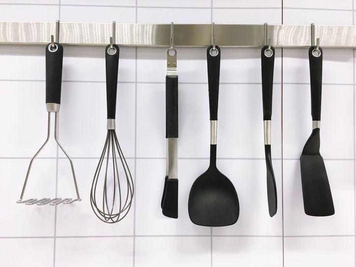 Close-up of kitchen utensils hanging on rack