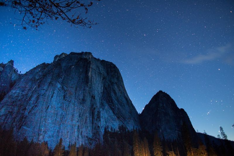 Low angle view of rocky mountains against star field at yosemite national park