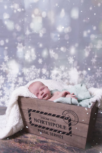 Cute baby boy sleeping in crate at home