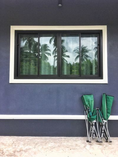 The folding bed is placed on the wall of the house, with a shadow of coconut trees in the mirror
