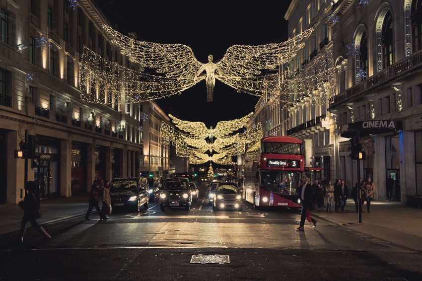 Cars and buses queuing up at traffic lights underneath Christmas lights in the shape of flying angels, people walking by in front of the stood cars. Adult Angel Lights Architecture Building Exterior Built Structure Canon 5d Mark Lll Christmas Christmas Angel Christmas Decoration Christmas Lights City England Flying Angel Illuminated Large Group Of People London London Bus Night Outdoors People People Commuting Streets At Christmas Streets At Night Travel Destinations Underneath Angels EyeEm Diversity