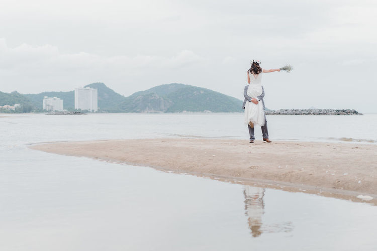 Man carrying woman while standing at beach against sky