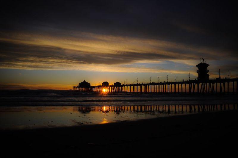 Huntington beach pier by sea against sky during sunset