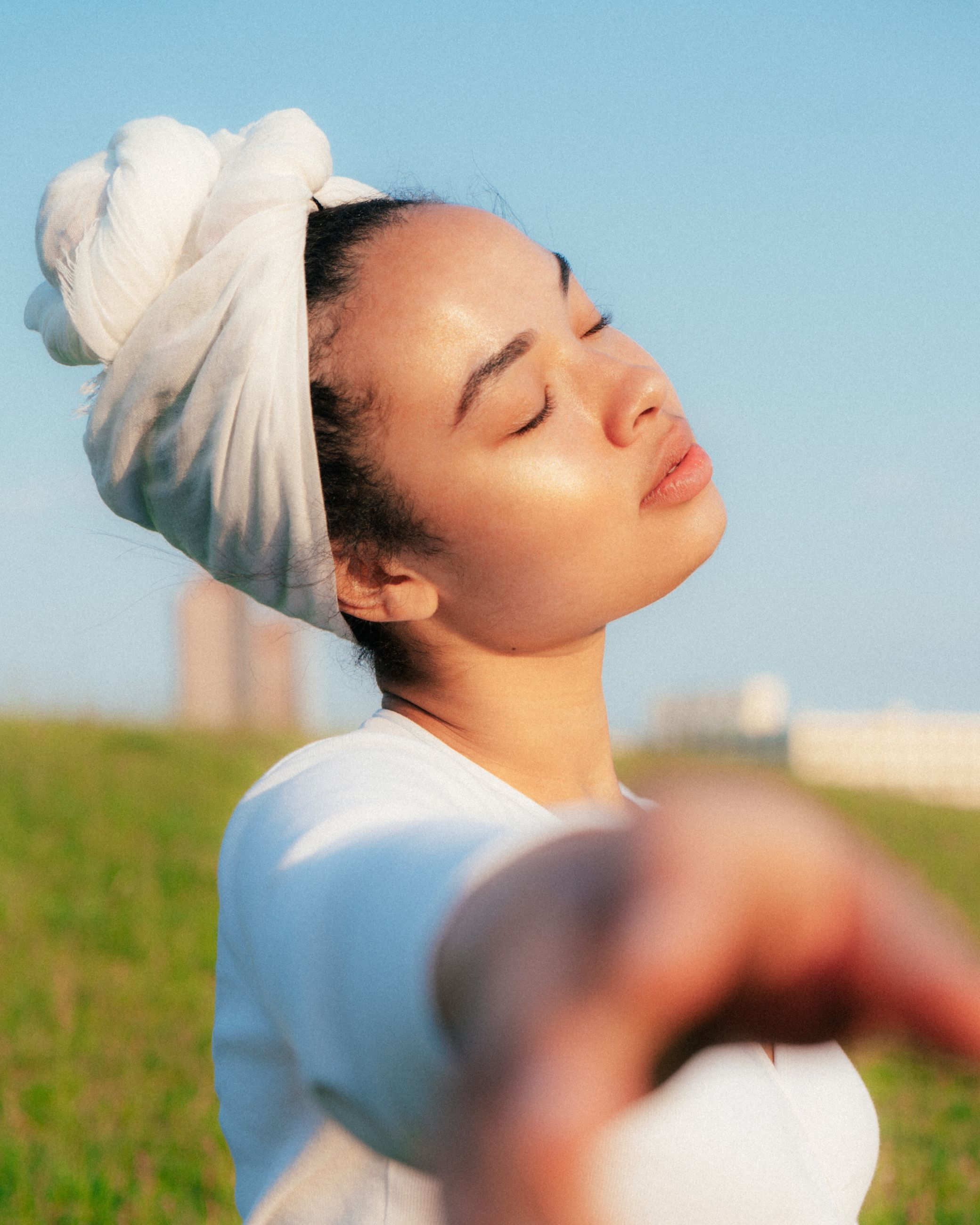 real people, leisure activity, one person, lifestyles, nature, eyes closed, sky, land, day, headshot, field, young women, grass, sunlight, young adult, women, focus on foreground, clear sky, hairstyle, outdoors, beautiful woman
