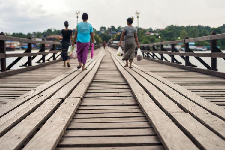 Rear view of people walking on footbridge