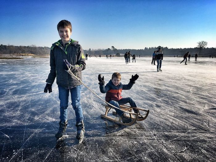 Winter Leisure Activity Snow Blue Sky Full Length Outdoors Nature Cold Temperature Real People Childhood Togetherness Day Beauty In Nature Beach Warm Clothing People Ice Skate Adult Uniqueness
