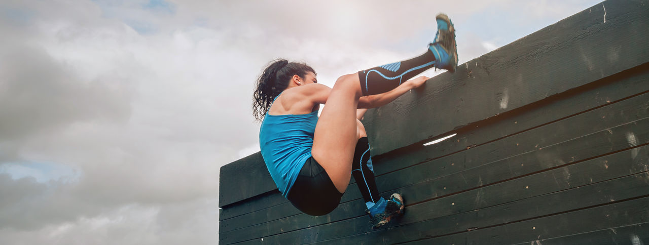 Low angle view of sporty woman climbing wooden wall against sky