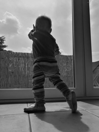 Rear view of baby girl standing by door at home