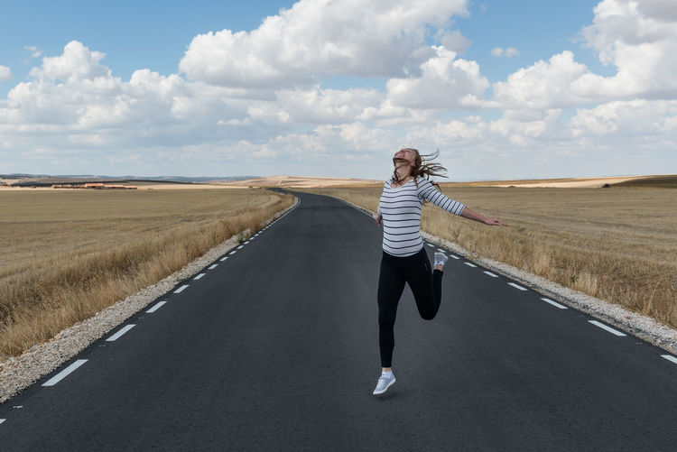 Woman jumping on road against sky