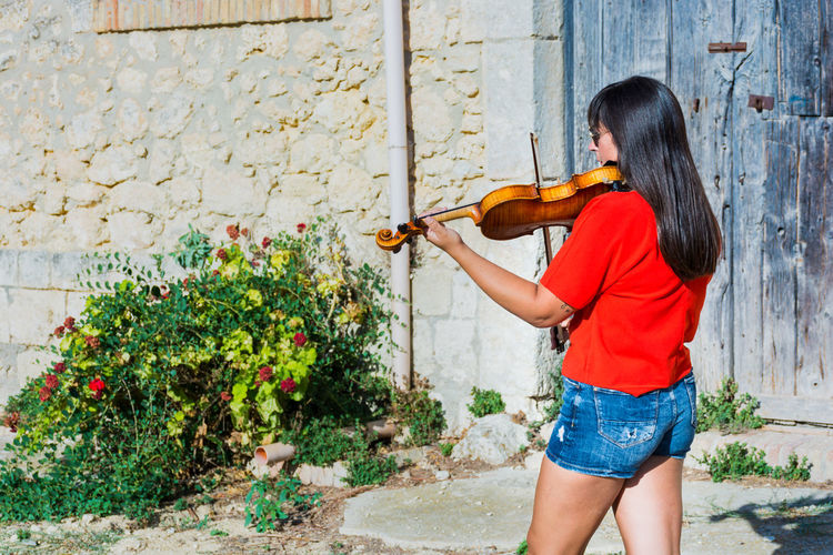 Woman Playing Violin While Standing Outdoors