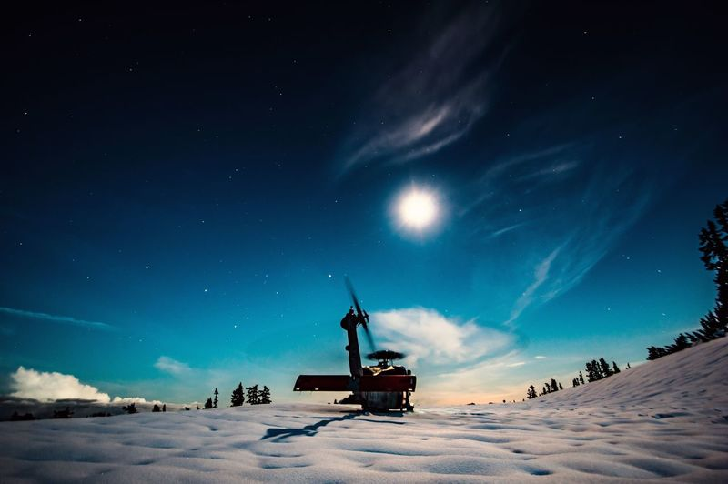 Helicopter On Snowy Hill Against Blue Sky At Dusk