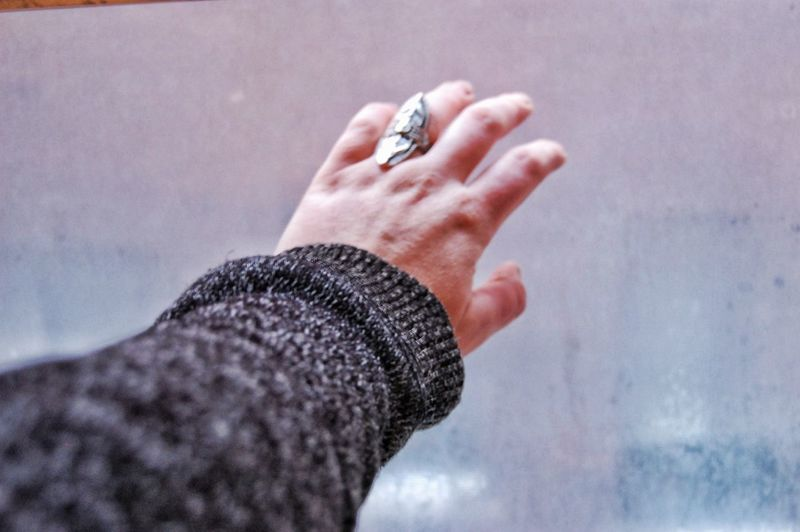 Cropped Hand Of Woman Gesturing Against Wet Window During Rainy Season