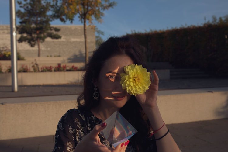 Portrait of young woman holding flower and prism while standing outdoors