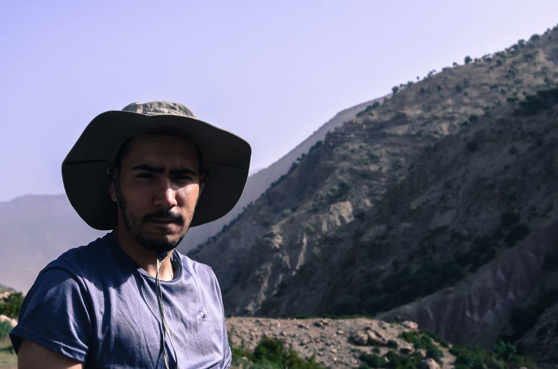 Portrait of young man standing against mountains