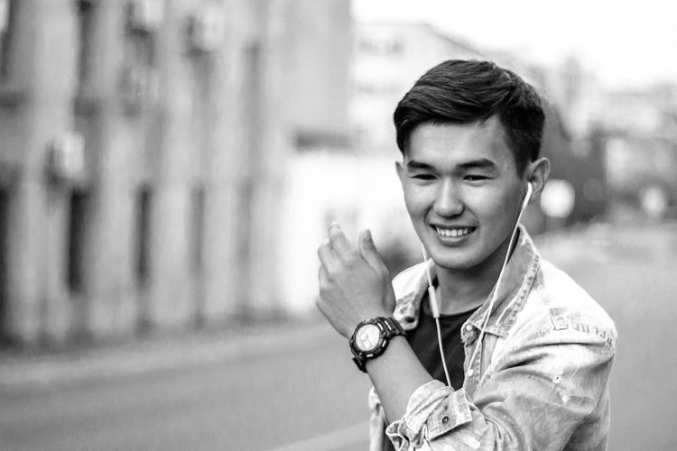 Smiling Young Man Listening Music While Standing On City Street