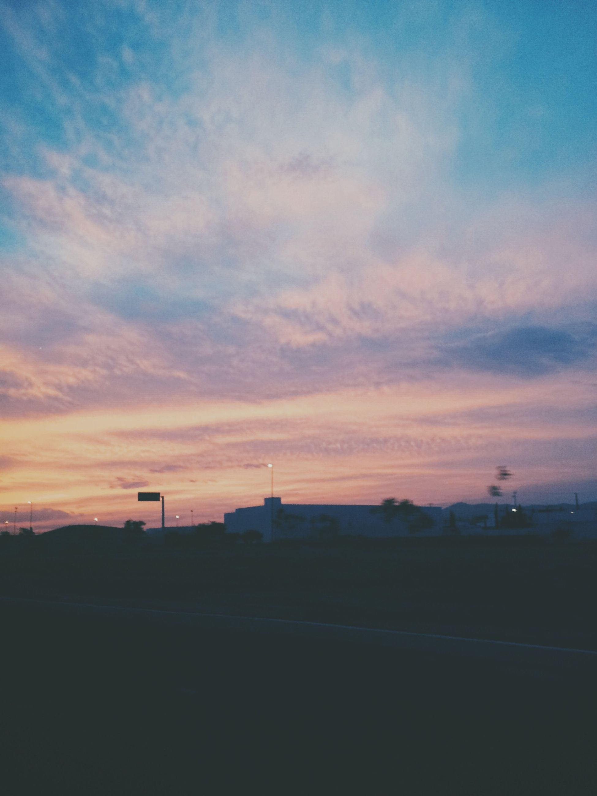 sunset, sky, silhouette, cloud - sky, building exterior, architecture, built structure, orange color, scenics, beauty in nature, dusk, cloud, landscape, tranquility, transportation, nature, tranquil scene, cloudy, outdoors, road
