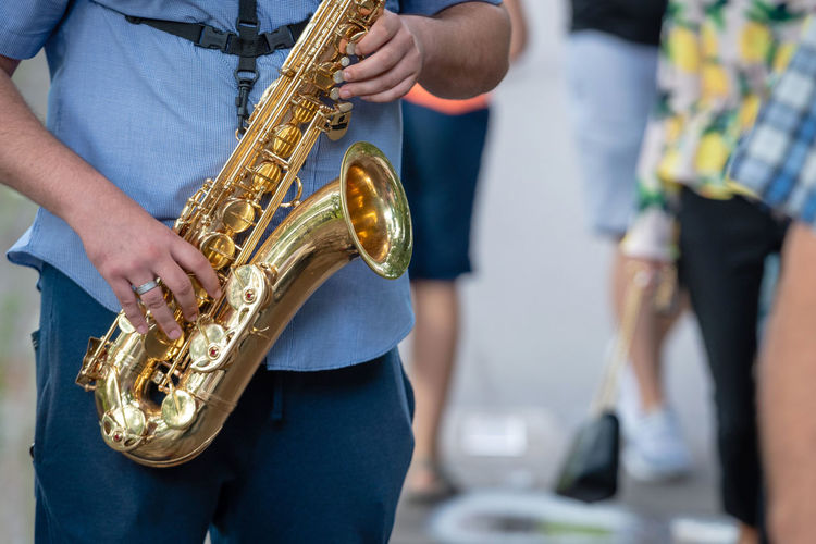 The street musician playing saxophone. Hands Jazz Music Sound Artist Arts Culture And Entertainment Day Focus On Foreground Gold Colored Holding Instrumental Men Midsection Music Musical Instrument Musician Occupation People Performance Playing Real People Saxophone Saxophonist Skill  Standing