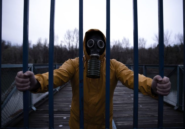 Man wearing gas mask while standing by metal against sky