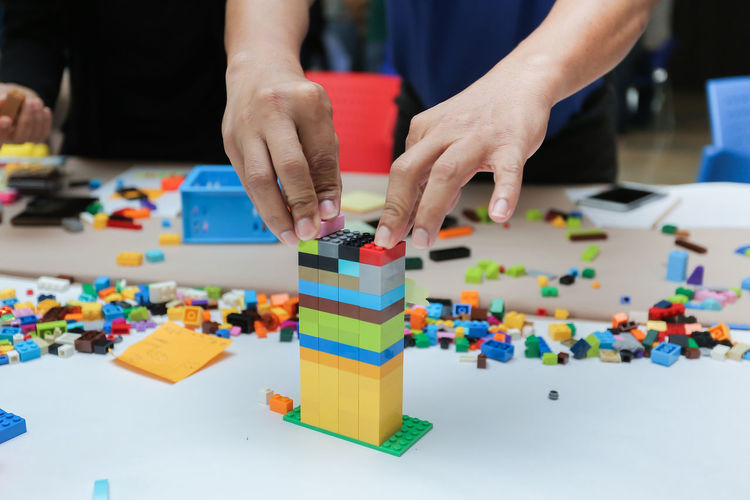 Lego blocks to be assembled to build a town,success team work Business Construction Event LEGO Teamwork Activity Block Brick Building Businessman Colorful Concept Connect Create Design Education Entertainment Hand Legophotography People Plactic Playing Team Town Toy