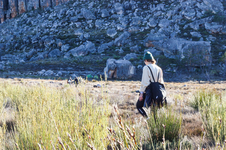 Hiker walking towards wilderness campsite in the mountains Adventure Beanie Camping Campsite Explore Female Grass Hike Hiker Landscape Landscape_Collection Let's Go. Together. Mountain Nature Outdoors Rock - Object Rock Formation Shadow Tent Walk Wilderness