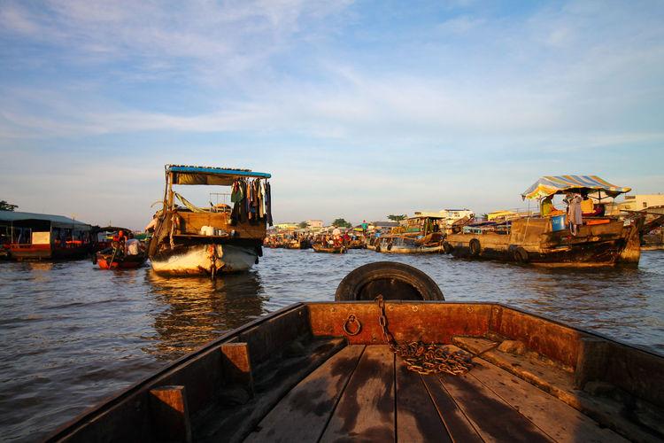 Merchant ship in cai rang floating market against sky
