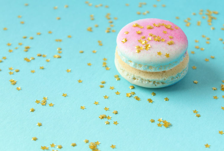 Close-up of macaroon and star shaped sequins on blue background
