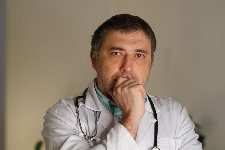 Portrait Of Thoughtful Mature Doctor Against Wall
