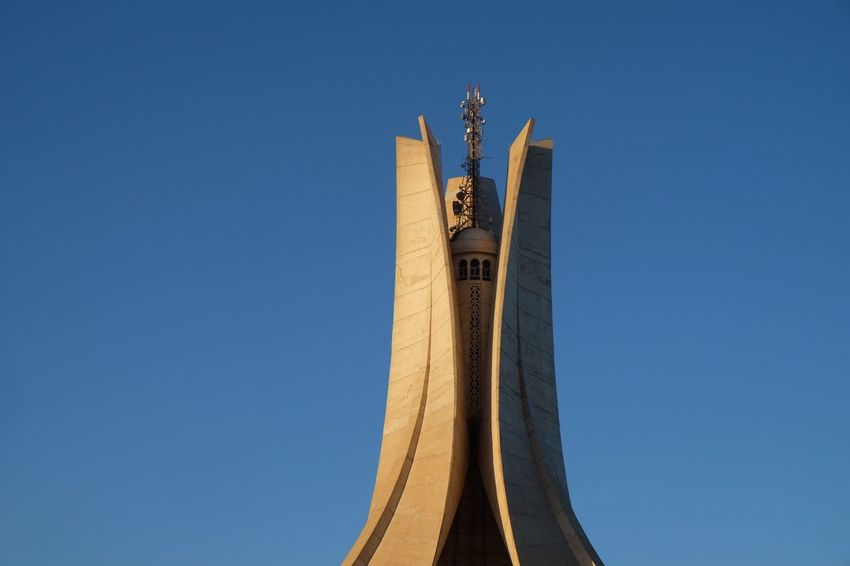 EyeEm Selects Blue Low Angle View Clear Sky Architecture Built Structure No People Day Flag Outdoors Makam Makam El Shahid Algiers Algerian Patriotism Revolution Statue Building Exterior Sculpture Sky