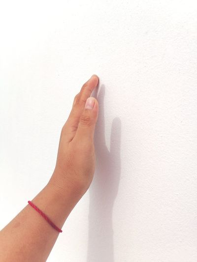 Close-up of hand against white wall