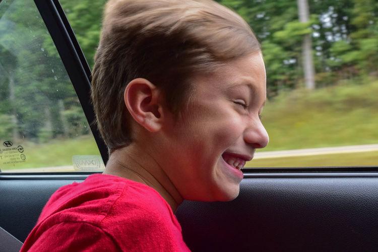 Happy boy looking through window of speeding car