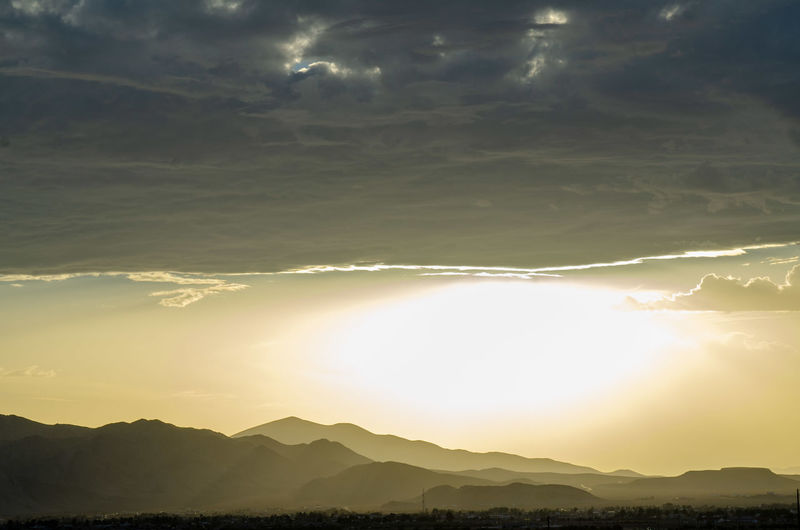 Mountain ranges, valleys, in silhouette under thick bank of rain clouds and a bright hazy sky