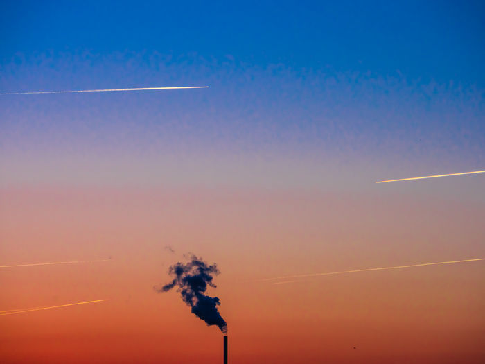 Silhouette smoke stack emitting against clear sky during sunset