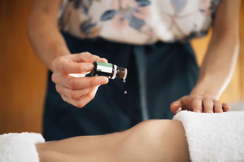 Ayurvedic therapist dropping ayurveda essential oil on female patient stomach