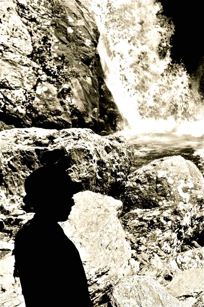 rock - object, real people, nature, sunlight, day, cave, one person, outdoors, beauty in nature, motion, standing, water, waterfall, people