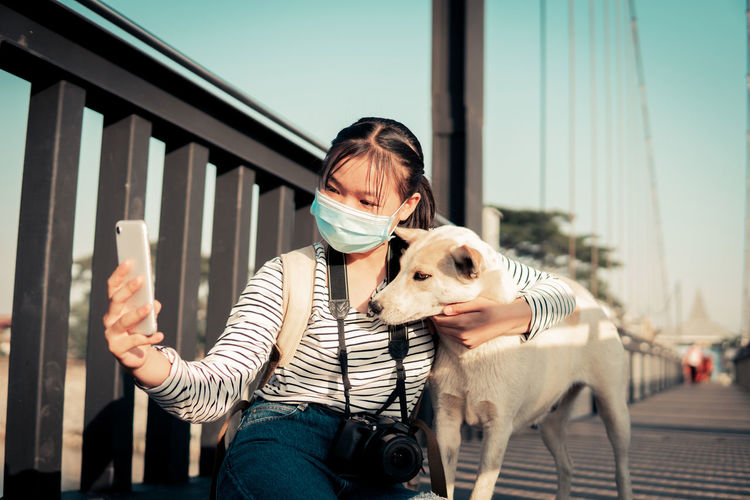 Woman with dog on mobile phone