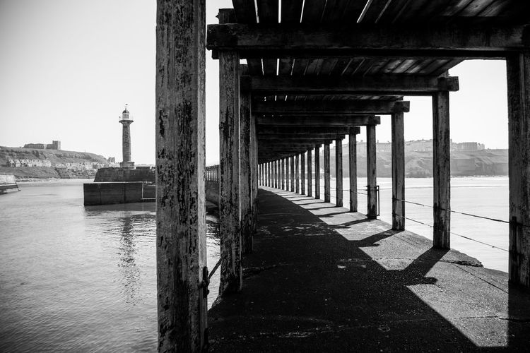 Under the pier Whitby Architectural Column Architecture Blackandwhite Bridge Bridge - Man Made Structure Built Structure Colonnade Connection Day In A Row Nature No People Outdoors Pier River Sky Sunlight Transportation Underneath Water Whitby Pier Wood - Material Wooden Post
